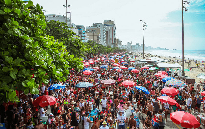 Banda e bloco desfilando na praia do Rio