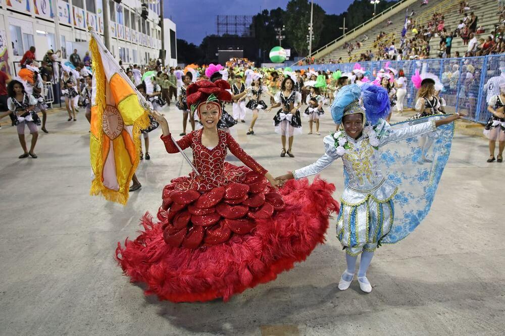 Crianças desfilando com uma escola de samba mirim do Rio de Janeiro