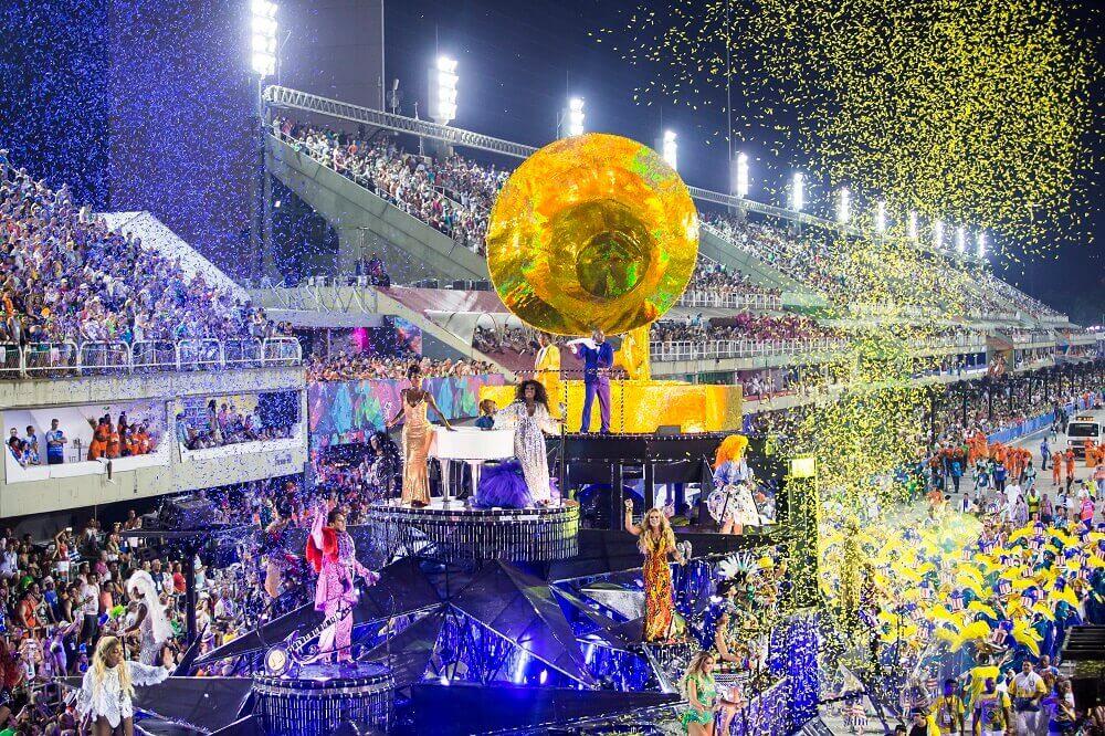 Carro alegórico desfilando no sambódromo do Rio em meio a confetes